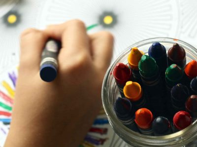 Kind malt mit Kreidestiften auf ein Blatt Papier